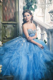 Beautiful young woman in gorgeous blue long dress like Cinderella with perfect make-up and hair style Royalty Free Stock Image