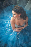 Beautiful young woman in gorgeous blue long dress like Cinderella with perfect make-up and hair style Royalty Free Stock Photos