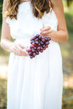 Beautiful young woman with grape bunches against Stock Photography