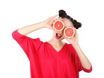 Beautiful young woman with grapefruit halves near eyes. On white background stock photography