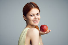 Beautiful young woman on a gray background holding an apple Royalty Free Stock Images
