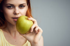 Beautiful young woman on a gray background holding an apple Stock Photos