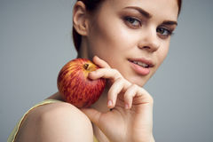Beautiful young woman on a gray background holding an apple Royalty Free Stock Photo