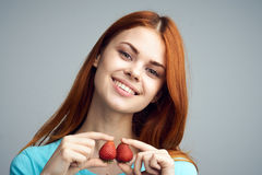 Beautiful young woman on a gray background holds a strawberry, smile, portrait Royalty Free Stock Image
