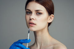 Beautiful young woman on a gray background holds a syringe, medicine, plastic Stock Images