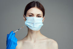 Beautiful young woman on a gray background holds a syringe, medicine, plastic Royalty Free Stock Images