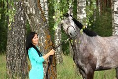 Beautiful young woman and gray horse portrait. In forest Royalty Free Stock Photo