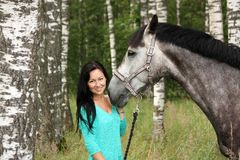 Beautiful young woman and gray horse portrait. In forest Stock Images