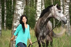 Beautiful young woman and gray horse portrait. In forest Stock Photography