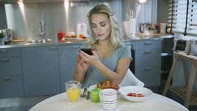 Woman using smartphone during breakfast. Beautiful young woman in gray T-shirt browsing smartphone while having nice breakfast in stylish kitchen stock video footage