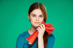 Beautiful young woman on a green background holds rubber gloves, cleaning, housework.  Stock Images