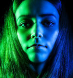 Beautiful young woman in green and blue lights. Over black background Stock Image