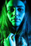 Beautiful young woman in green and blue lights. Over black background Stock Photography