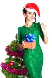 Beautiful young woman in a green dress and Christmas hat with a Royalty Free Stock Image