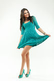Beautiful young woman in a green dress with curly long hair Stock Photos