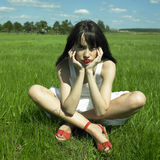 Beautiful young woman on a green field Stock Image