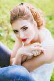 Beautiful young woman on a green football field. Closeup portrait of. Red lips. Stock Image