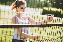 Beautiful young woman on a green football field. Girl standing at football gate, dressed in blue jeans, a white t-shirt Stock Photos
