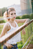 Beautiful young woman on a green football field. Girl standing at football gate, dressed in blue jeans, a white t-shirt Royalty Free Stock Images