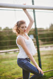 Beautiful young woman on a green football field. Girl standing at football gate, dressed in blue jeans, a white t-shirt Stock Photography