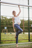 Beautiful young woman on a green football field. Girl standing at football gate, dressed in blue jeans, a white t-shirt Royalty Free Stock Image