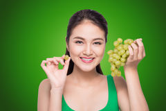 Beautiful young woman with green grape isolated on green backgro. Und Royalty Free Stock Photos
