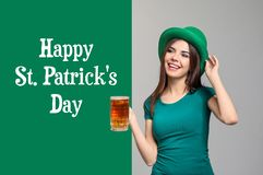 Beautiful young woman in green hat and with mug of beer on grey background. St. Patrick\'s Day celebration royalty free stock images