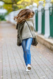 Beautiful young woman in green knitted cardigan with a hood walking in autumn park. Autumn fashin concept. Royalty Free Stock Photo