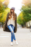 Beautiful young woman in green knitted cardigan with a hood walking in autumn park. Autumn fashin concept. Royalty Free Stock Image