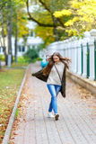 Beautiful young woman in green knitted cardigan with a hood walking in autumn park. Autumn fashin concept. Royalty Free Stock Photos