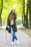 Beautiful young woman in green knitted cardigan with a hood walking in autumn park and talking mobile phone. Autumn Stock Photo
