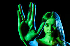 Beautiful young woman in green light showing the alien sign Stock Images