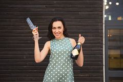 Beautiful young woman in a green polka dots dress holding two glasses and champagne bottle. Outdoor. Party time stock image