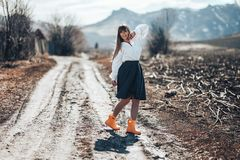 A beautiful young woman in a grey skirt and rubber boots walks through a meadow in country. She dances, laughing has fun and. Radiates freedom stock photos