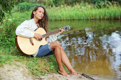 Beautiful young woman with guitar. On the river coast Royalty Free Stock Images