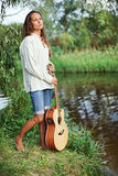 Beautiful young woman with guitar. On the river coast Royalty Free Stock Image