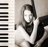 Beautiful young woman with guitar, piano Stock Photo