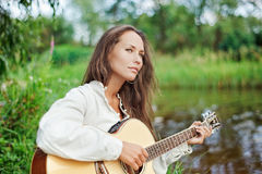 Beautiful young woman with guitar on the river. Coast stock photos