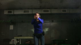 Beautiful young woman with the gun on an indoor shooting range. shoots a gun stock video footage