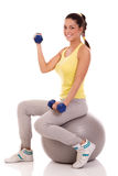 Beautiful young woman with gym ball exercising with dumb bells Stock Images