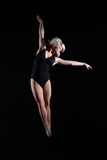 Beautiful young woman gymnast suspended in the air Stock Images