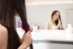 Beautiful young woman with hair brush near mirror stock images