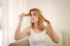 Beautiful young woman with hair loss problem. At home Royalty Free Stock Photo
