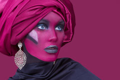 Beautiful young woman with hair wrapped in turban. Creative portrait on red background Stock Photo