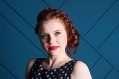 Beautiful young woman with hairdo and makeup. Is in blue studio Royalty Free Stock Photo