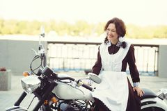 Beautiful young woman, hairstyle and bows outdoors with a motorcycle. Happy and healthy dressed in a Soviet school uniform. girl b Stock Photos