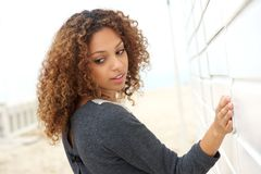 Beautiful young woman with hand on wall and looking over shoulder Royalty Free Stock Photos