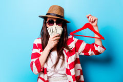 Beautiful young woman with hanger and money standing in front of Royalty Free Stock Image