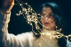 Beautiful young woman hanging christmas lights Royalty Free Stock Image