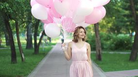 Beautiful young woman happily going on a summer park holding balloons. stock video